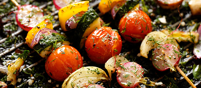 Grilled veggie skewers with cherry tomatoes, radishes, peppers and onions with fresh dill on a grill pan